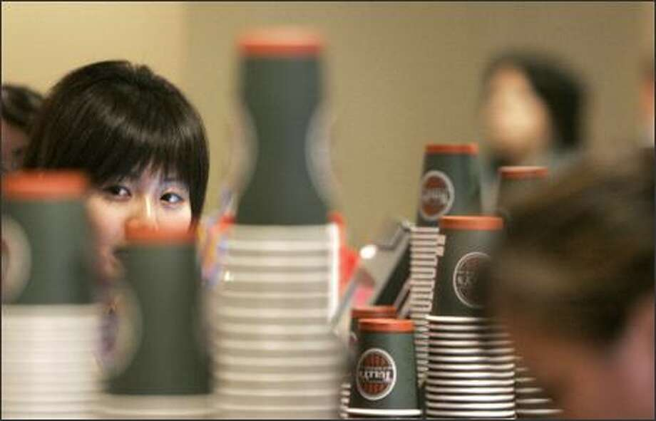 "UW freshman Rosemary Gong, 19, sells coffee on campus Wednesday. The university goes through about 5,000 paper cups a day, and a ""Sustainability Is Sexy"" campaign has been launched asking students to use their own coffee cups instead of paper cups. Photo: Meryl Schenker, Seattle Post-Intelligencer / Seattle Post-Intelligencer"