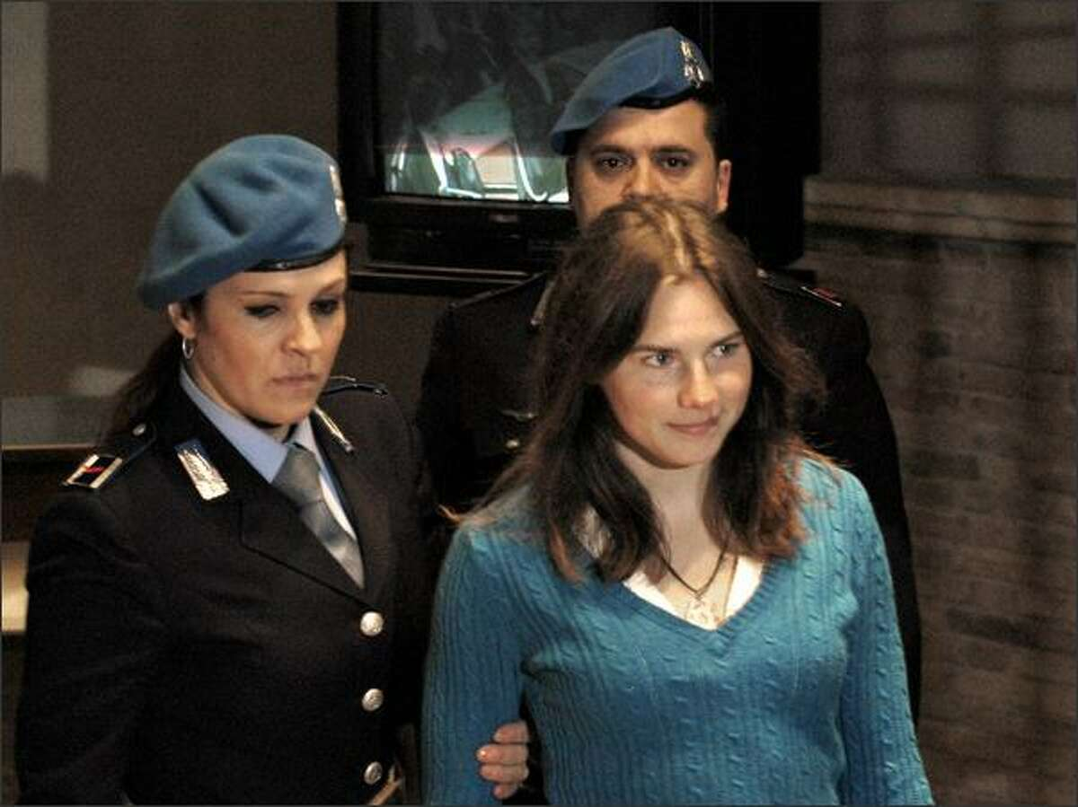 U.S. murder suspect Amanda Knox, right, is escorted into a courtroom to stand trial in Perugia, Italy, on Saturday, Feb. 28, 2009. Knox, and Knox's former Italian boyfriend, Raffaele Sollecito, are being tried on charges of sexual violence and murder of her British roommate Meredith Kercher in Perugia in November 2007. Both deny wrongdoing. (AP Photo/Stefano Medici)