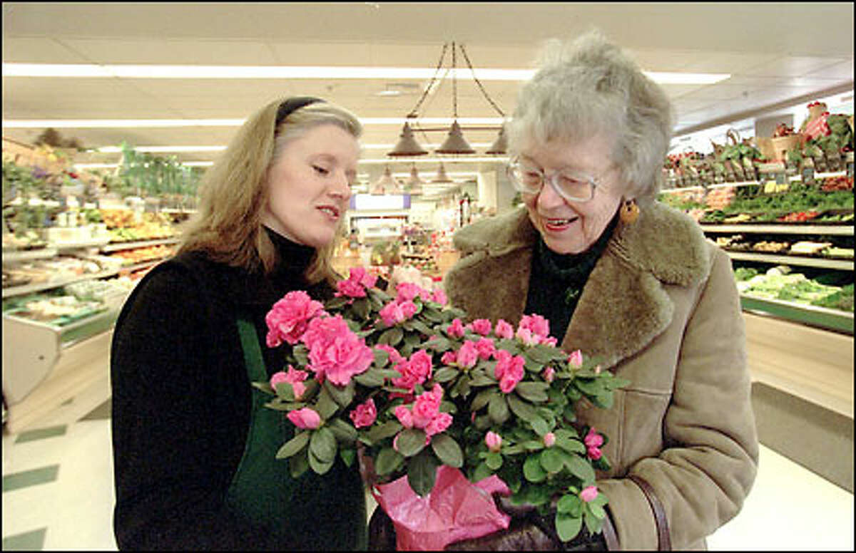 Polly Clark, right, shows Lillian Cawdrey, co-owner of Fremont Fresh Market, an azalea she is buying for a friend.