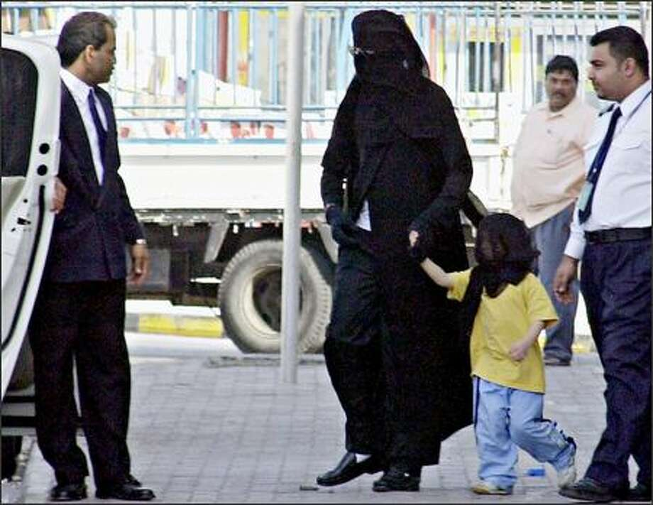 Someone please tell Michael Jackson that, traditionally, only women need wear the full-body covering known as the abaya in Muslim countries such as Bahrain. But maybe M.J. finally has found a place where it's normal to veil the faces of his children and his body due to his skin condition, vitiligo. (HASAN JAMALI/AP) Photo: Associated Press / Associated Press