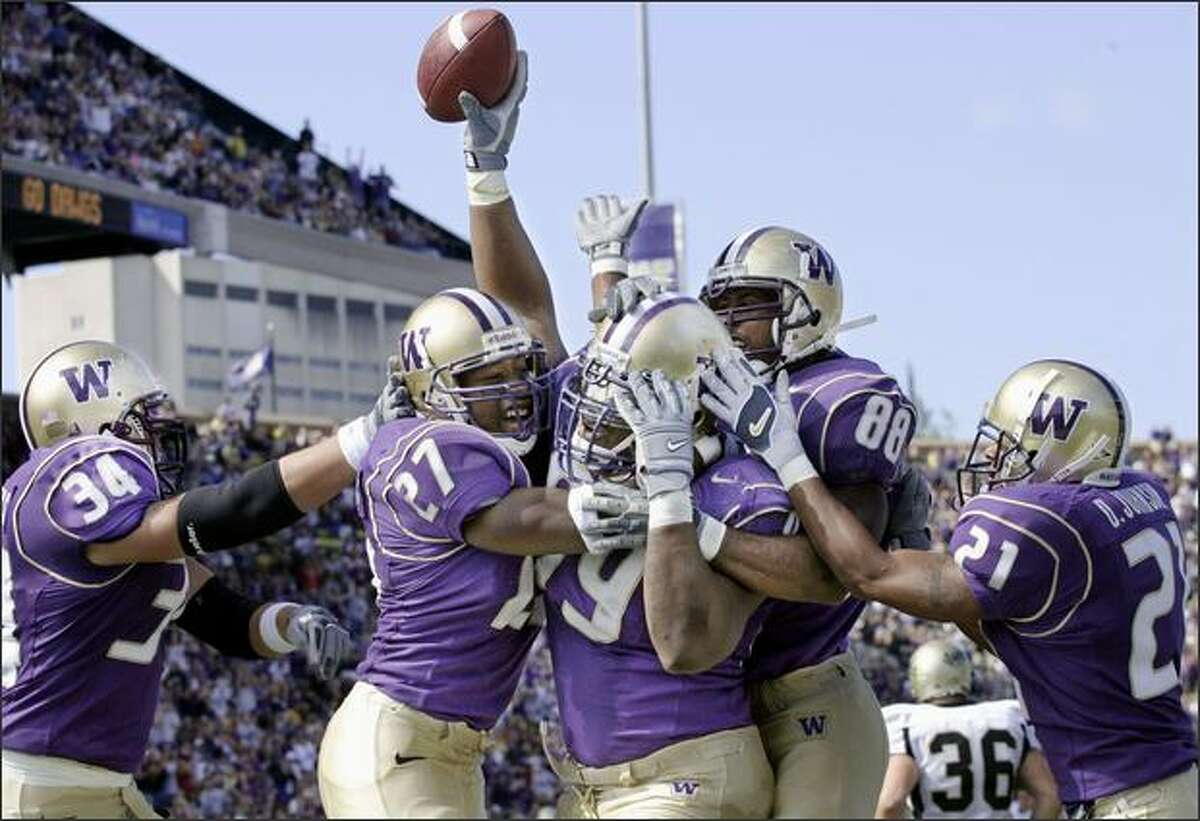 Washington's Terry Johnson, center holding ball, celebrates with Greg Crothers (34) Evan Benjamin (27) Marquis Cooper (88) and Derrick Johnson (21) after recovering a fumble in the endzone to score in the first quarter against Idaho at Husky Stadium in Seattle on Sept. 20, 2003. Washington won 45-14.