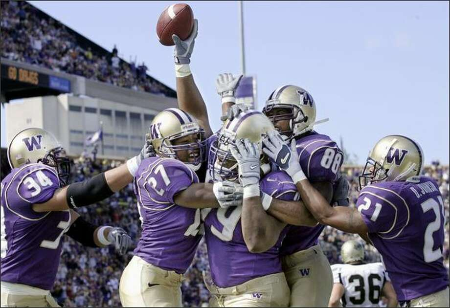 Washington's Terry Johnson, center holding ball, celebrates with Greg Crothers (34) Evan Benjamin (27) Marquis Cooper (88) and Derrick Johnson (21) after recovering a fumble in the endzone to score in the first quarter against Idaho at Husky Stadium in Seattle on Sept. 20, 2003. Washington won 45-14. Photo: Associated Press / Associated Press