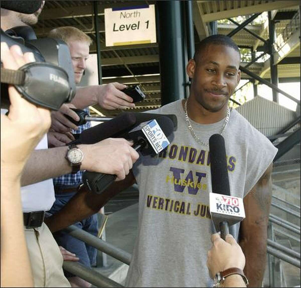 University of Washington linebacker Marquis Cooper passes by waiting reporters as he arrives for a meeting with head football coach Rick Neuheisel at Huskey Stadium in Seattle on June 5, 2003. Cooper and three others are missing in a boat off Floriday's Gulf Coast.