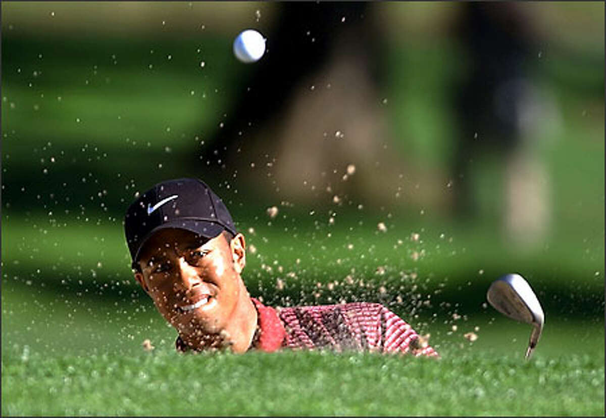 Tiger Woods hits from a bunker on the 29th hole of his finals match against David Toms in the Accenture Match Play Championship at La Costa Resort in Carlsbad, Calif., Sunday, March 2, 2003.