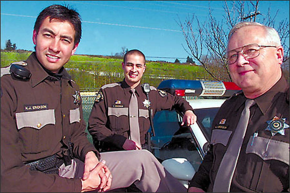From left, Deputy Kraig Erickson, younger brother Deputy Leigh Erickson and their father, Sgt. Larry Erickson, are shown recently at the King County Sheriff's Office special operations headquarters near Boeing Field.