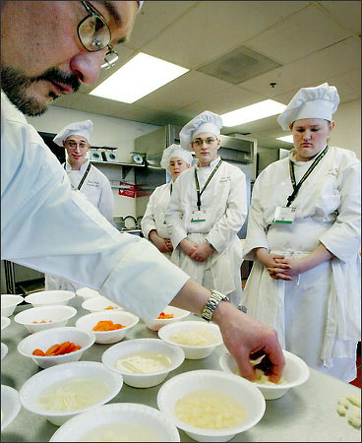 Enumclaw students (from left) Kevin Deane, Julianne Crane, Joshua Oster and Tara Ford watch as judge Gregg Shiosaki, a chef instructor at North Seattle Community College, critiques the quality and consistency of the vegetables the students cut in the knife skills portion of the Hospitality Invitational.