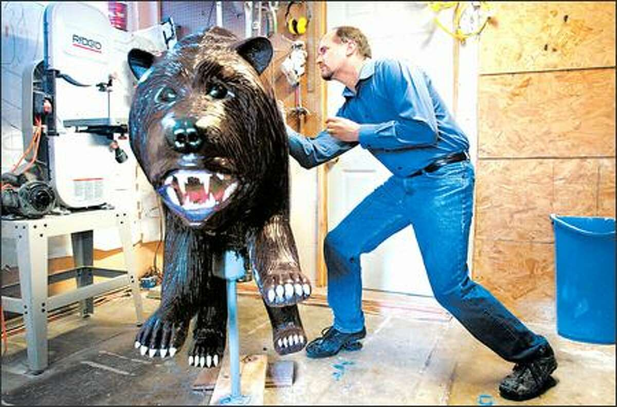 In his Poulsbo shop, Brent White finishes up a bear destined for a new carousel at the Indianapolis Zoo. His twin brother, Bruce, in Missouri, also created models of various animals.