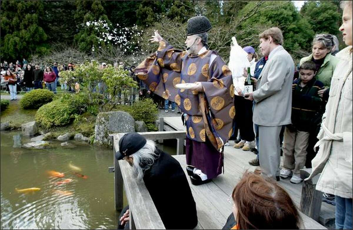A crowd watches as the Rev. Koichi Barrish, of the Tsubaki Shinto Shrine, tosses a mixture of salt, rice, paper and sacred sand to purify the grounds of the Seattle Japanese Garden at the Arboretum during a blessing ceremony.