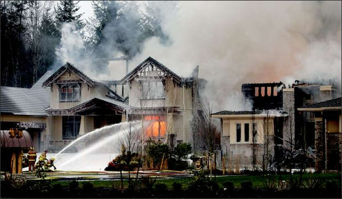 Firefighters spray water onto burning houses at the scene of where four multimillion dollar homes burned Monday in Woodinville. A sign with the initials of a radical environmental group was found at the scene, an official said.