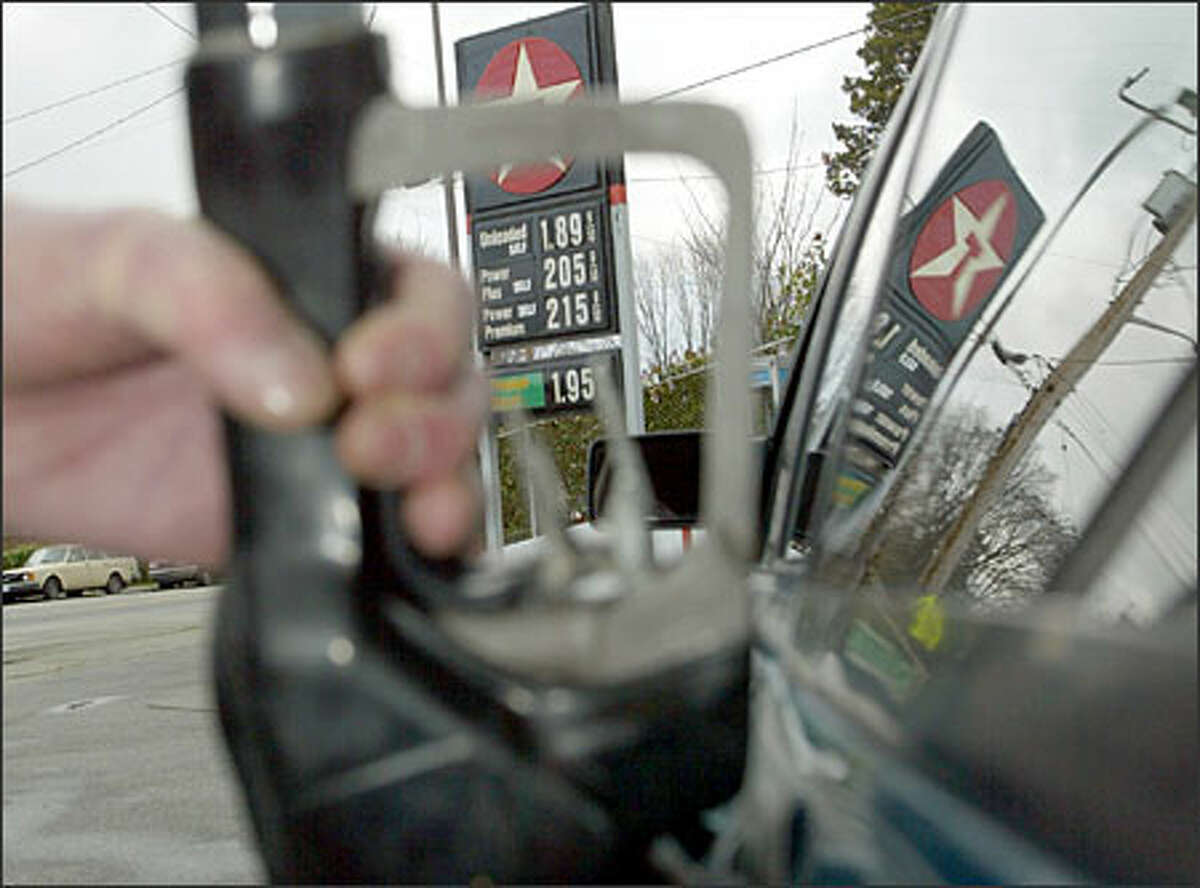 """Ric Kastner, who owns Ric's Automotive & Texaco Inc. in Magnolia, fills a gas tank at his station; his premium was selling for $2.15 9/10 a gallon yesterday. """"I have never seen them (gas prices) go up this high this fast,"""" he said."""