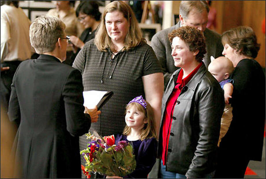 Karen Zeller Lane, left, and Janine Zeller Lane of Seattle, exchange wedding vows in Portland as their daughter DeLancey, 7, watches. Photo: Joshua Trujillo, Seattlepi.com / seattlepi.com