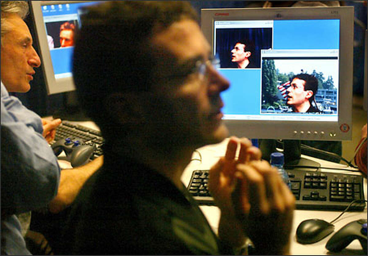 Antonio Criminisi, foreground, and Andrew Blake of the Microsoft Research office in Cambridge, England, demonstrate a program called i2i:3D Visual Communication, which uses two cameras to distinguish the primary speaker from the other parts of the picture tracking a person.