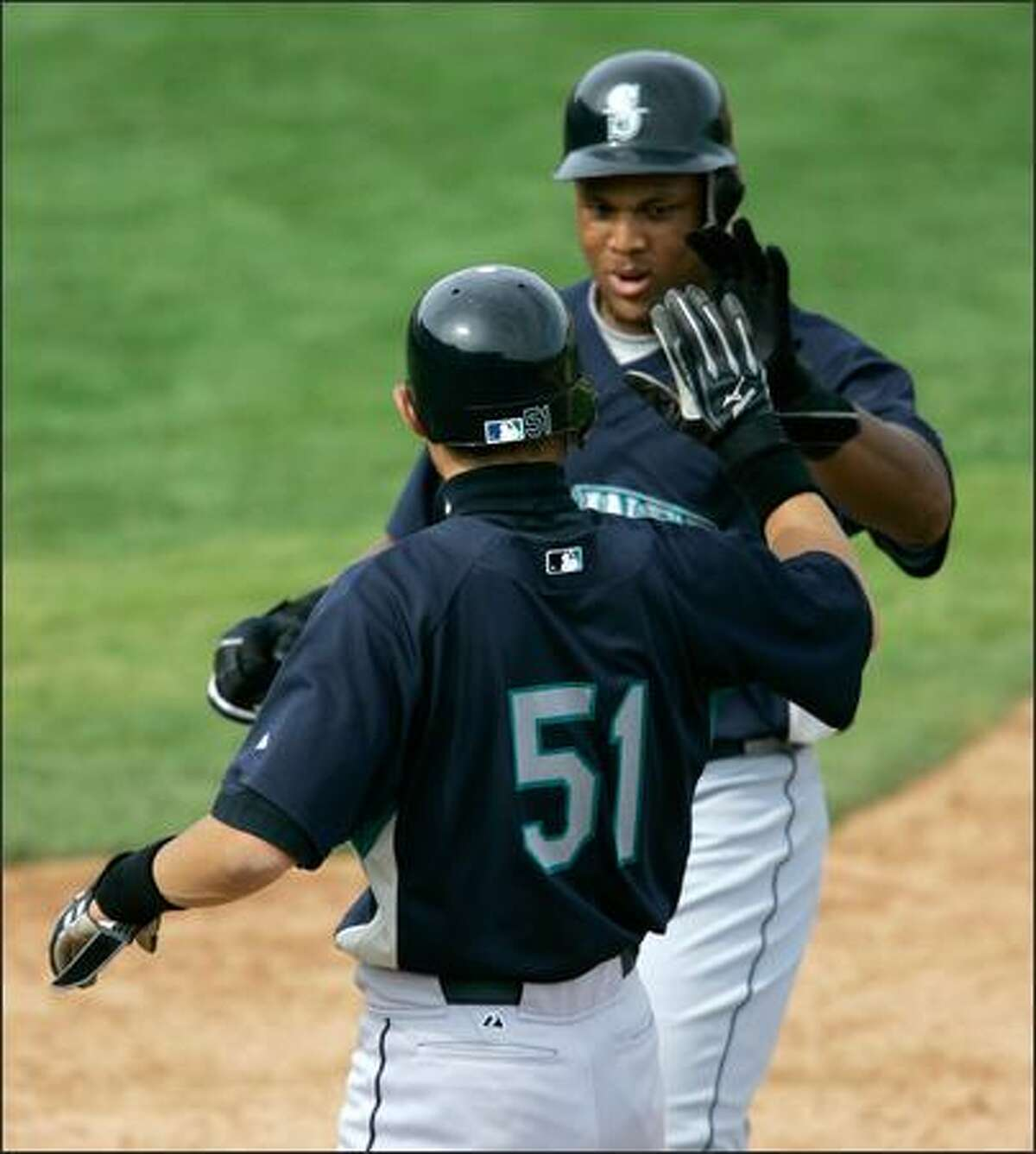 Adrian Beltre, right, seen here being greeted by teammate Ichiro Suzuki after hitting a homer Sunday, thrives on competition.