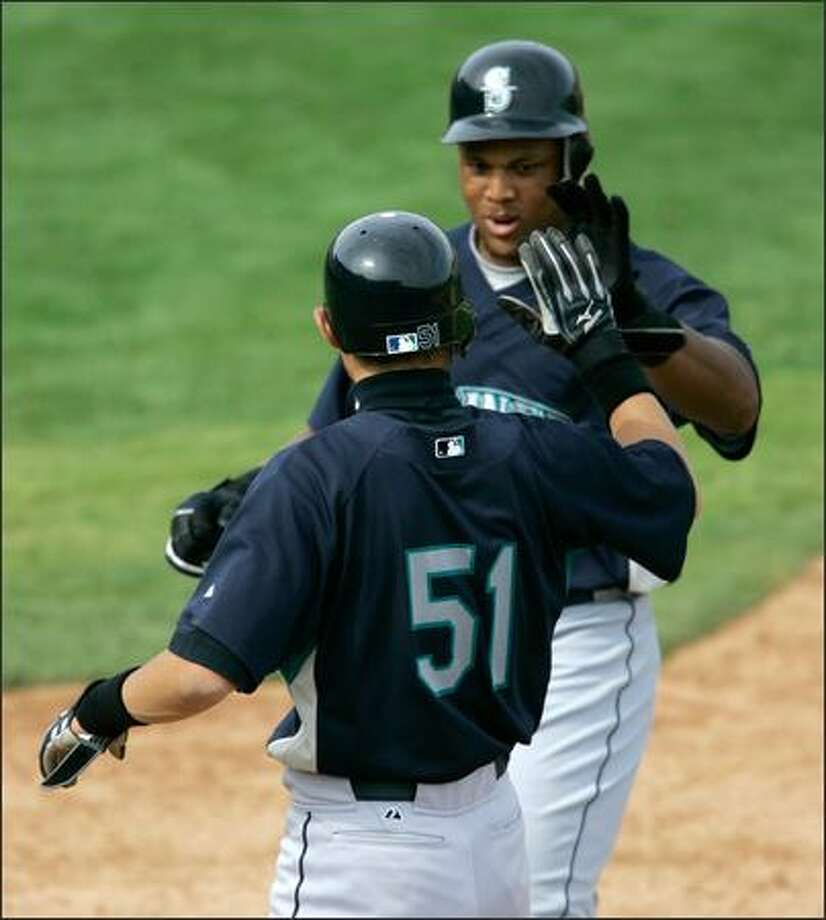 Adrian Beltre, right, seen here being greeted by teammate Ichiro Suzuki after hitting a homer Sunday, thrives on competition. Photo: Associated Press / Associated Press