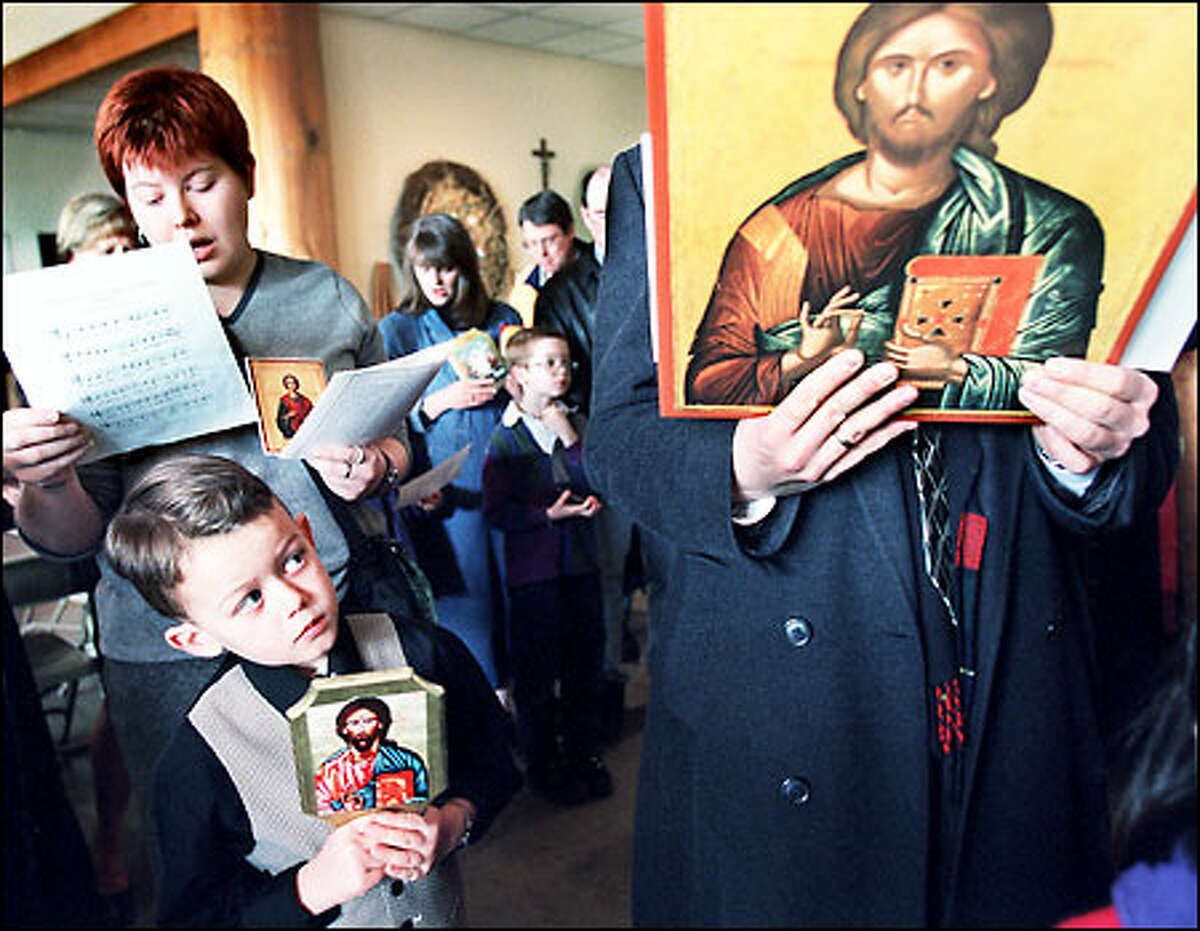 Forrest Goff, 6, front, and his aunt Alexia Johnson, behind him, participate in a service at the Greek Orthodox Mission parish in Kenmore. Eastern Orthodox Christians yesterday celebrated the