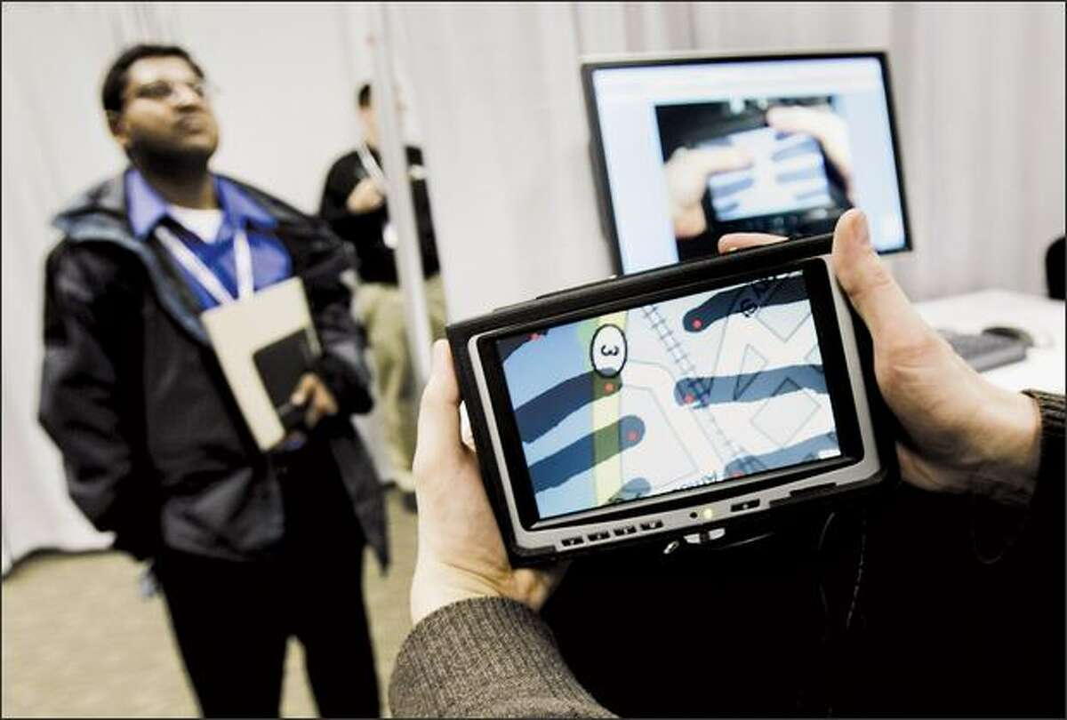 Prabal Dutta of the University of California-Berkeley listens as Patrick Baudisch of Microsoft Research demonstrates LucidTouch at the annual Microsoft Research TechFest in Redmond. LucidTouch is a prototype that doesn't let your fingers get in the way of the touch screen, instead allowing users to manipulate a portable device by touching the screen from behind. Microsoft introduced about 40 research projects Tuesday at a preview for media and academics.