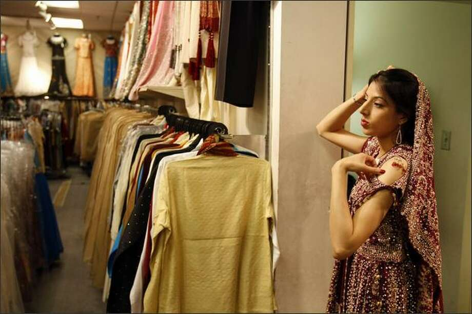 Ambreen Azeem came from Calgary to shop in Vancouver's Little India. She is trying on a wedding dress at Guru Bazaar. Photo: Meryl Schenker, Seattle Post-Intelligencer / Seattle Post-Intelligencer