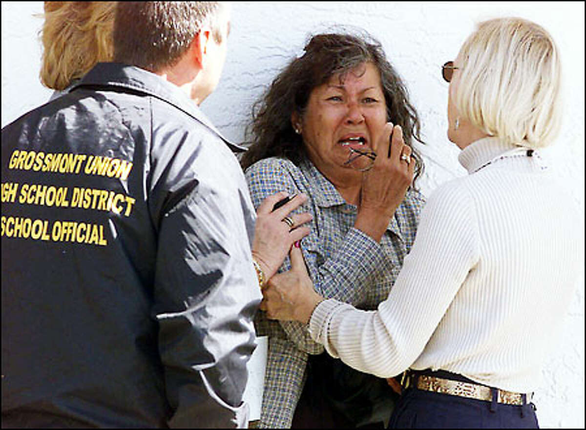 A woman is helped by grief counselors across the street from Santana High. Special counseling was also set up for students and school staff. (AP Photo/Los Angeles Times, Mark Boster)