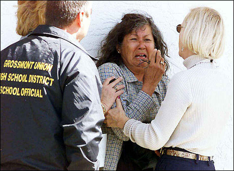 A woman is helped by grief counselors across the street from Santana High. Special counseling was also set up for students and school staff. (AP Photo/Los Angeles Times, Mark Boster) Photo: Associated Press / Associated Press