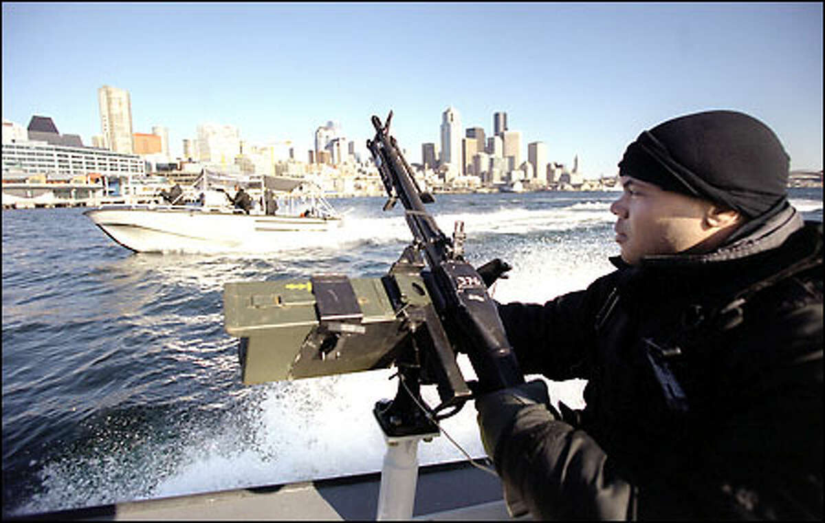 Coast Guard reservist Lewis Raynor Jr., a member of Port Security Unit 313, mans a machine gun while on patrol in a fast