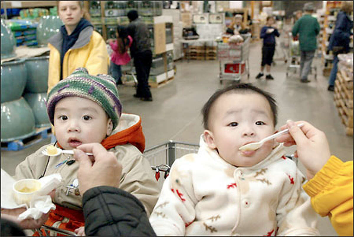 Grandmother Ru Deng Shao and mother Yi Li Wu serve free samples to Jia Jia Wu and Jessica Wu at the Costco store on Fourth Avenue South in Seattle.