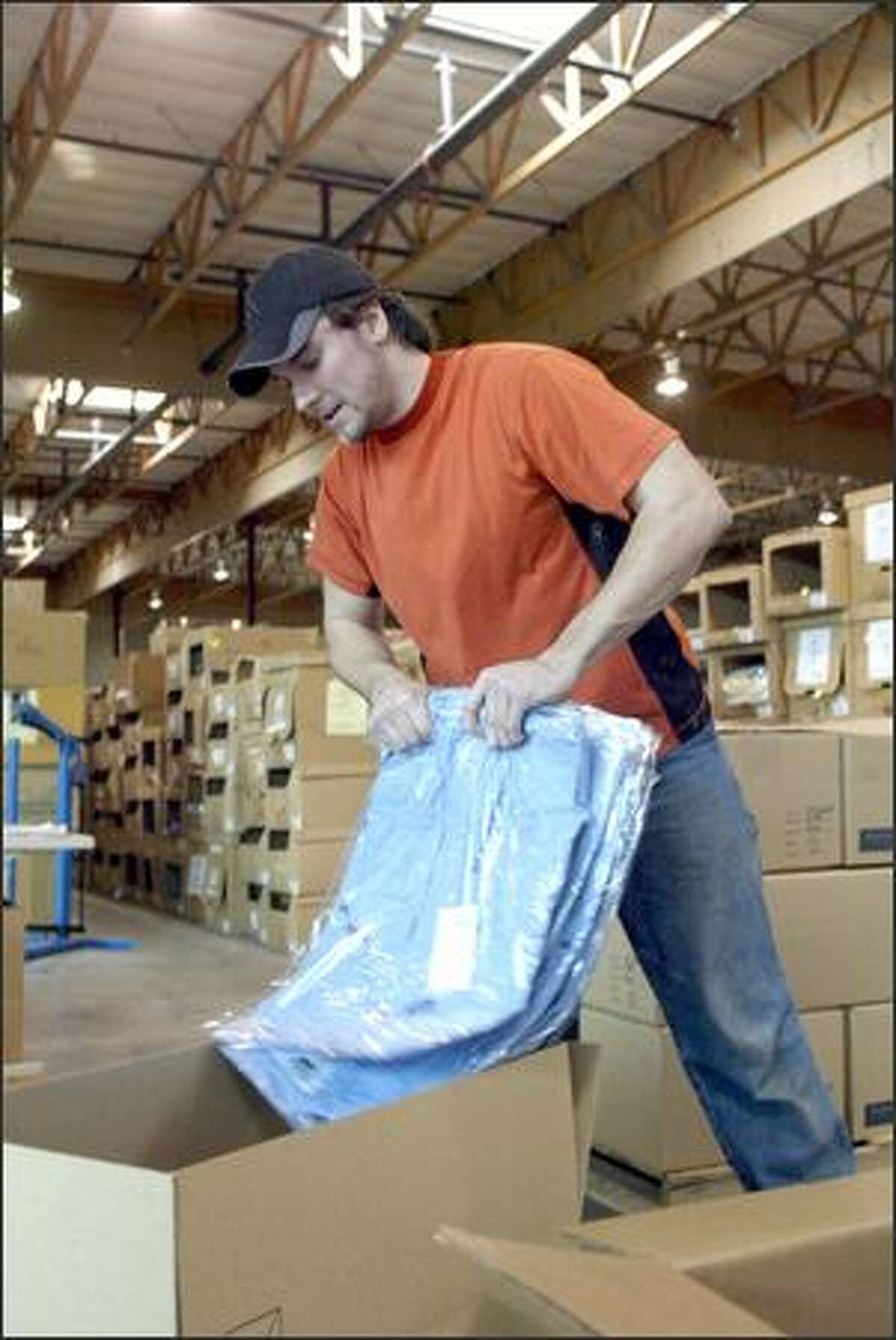 Dylan Morss packs shirts in the new Ex Officio headquarters in Tukwila. The company moved its headquarters to accommodate an expected increase in business.