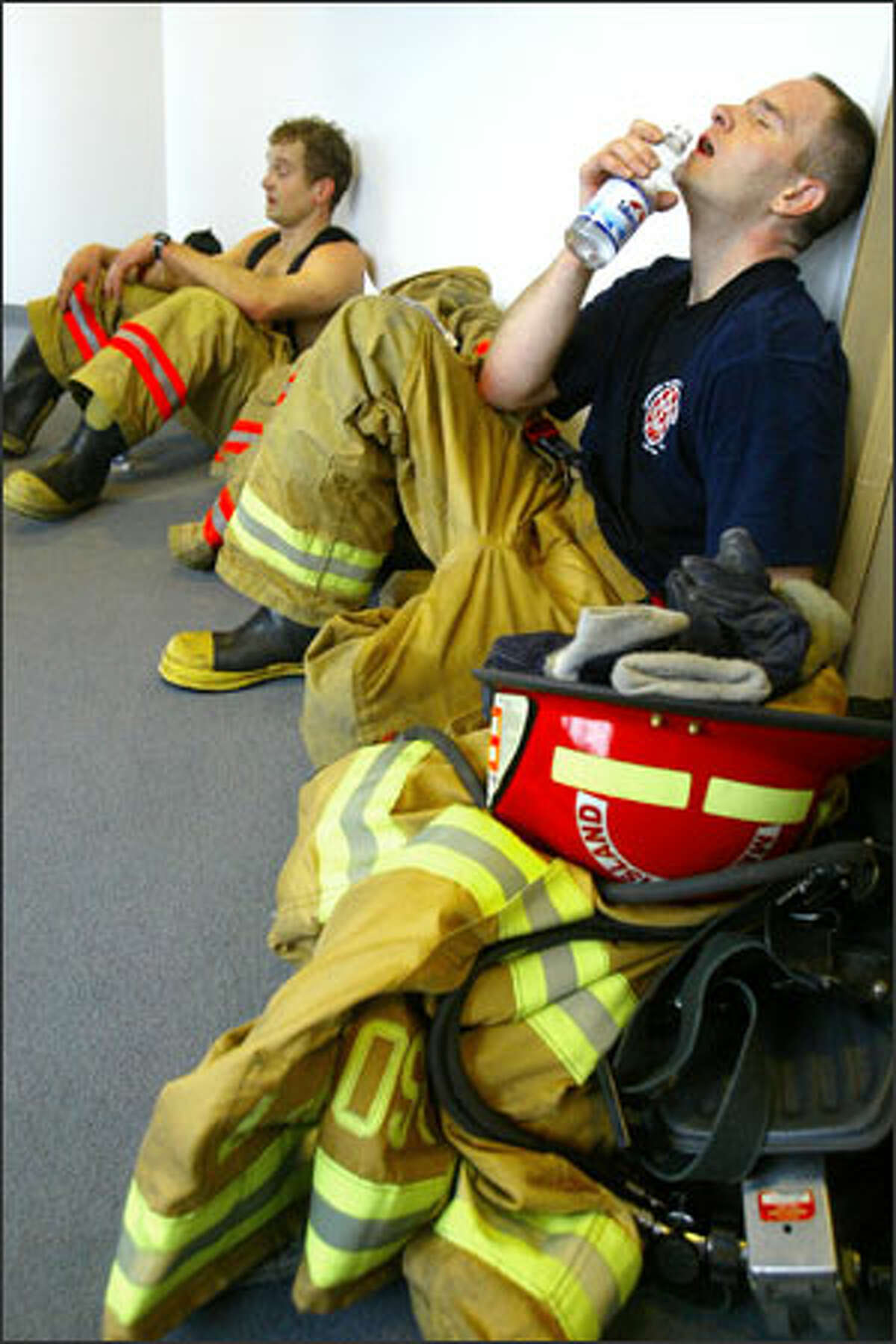 Mercer Island firefighter Curt Groscost rests after racing up 69 flights of stairs at Columbia Center.