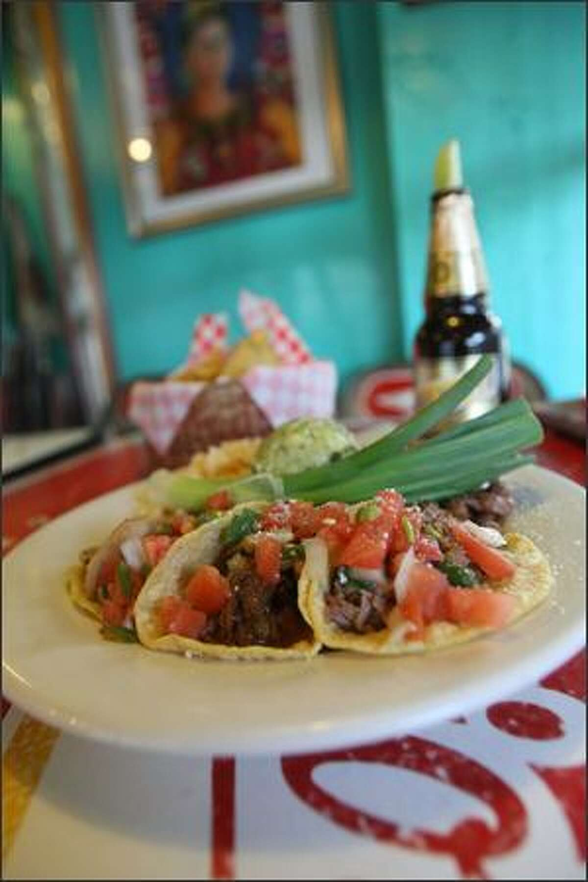 A combination taquito plate of carnitas, chicken and machaca is served with rice and beans at Le Puerco Lloron.
