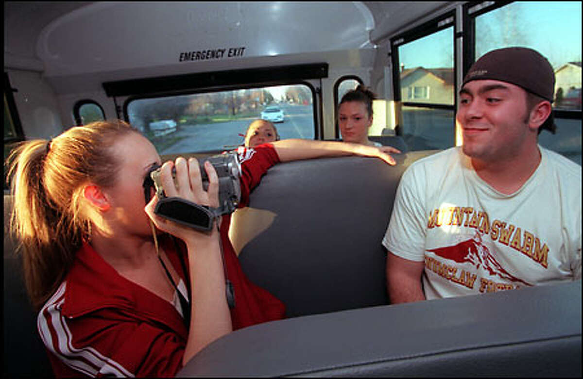 Brittney Osborn videotapes Jacob Wasson on the bus to the Tacoma Dome, where the Enumclaw boys' and girls' basketball teams will play in the WIAA 4A Basketball Championships.