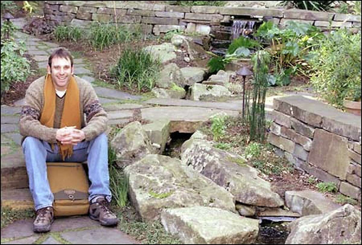 Cameron Scott, Exteriorscapes owner, shows off a garden in Queen Anne he designed that accentuates walls of Eagle Mountain rock.