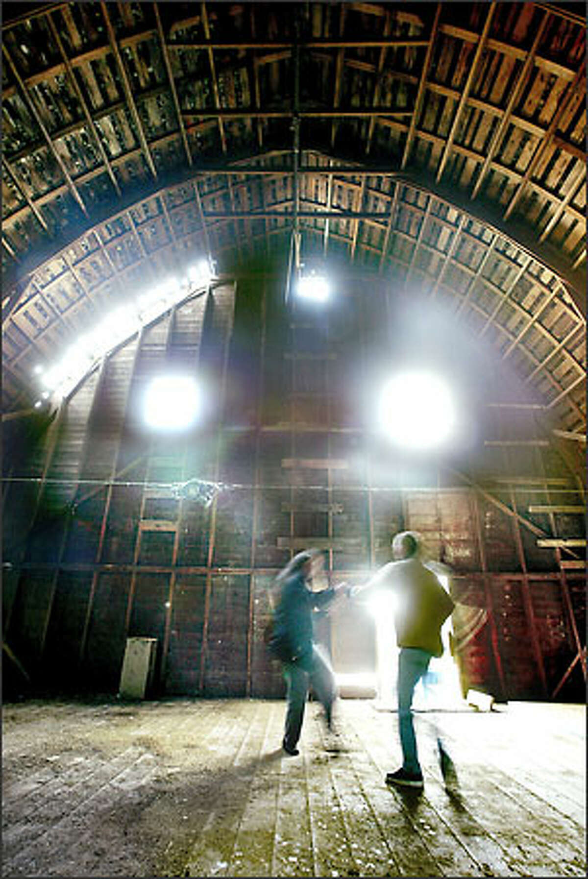 Lee Grumman, at left, and Paula McDonald, board members of the Duvall Foundation for the Arts, are a blur as they break into an impromptu dance during a visit Tuesday to the Thayer Barn in Duvall.