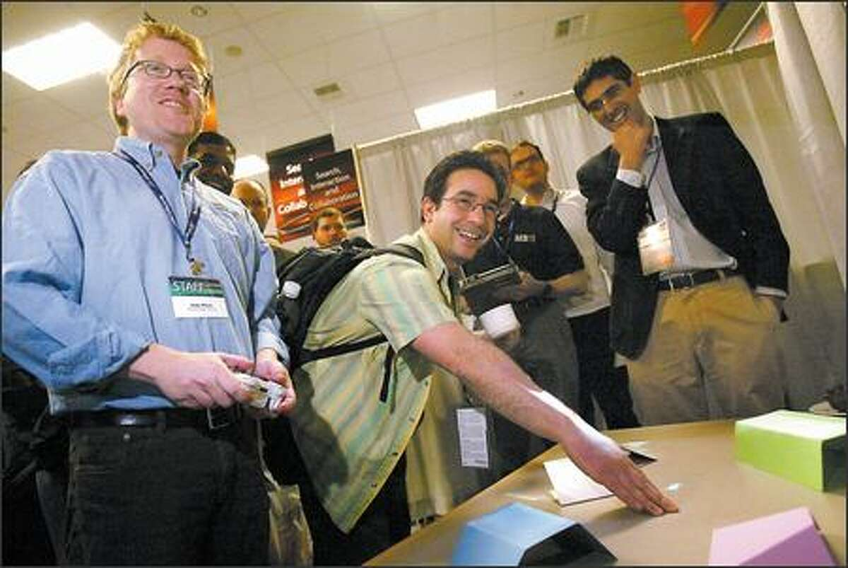 Andy Wilson, left, shows Alex Dimakis a prototype that lets people drive a tiny image of a car across and over real objects on a table at TechFest.