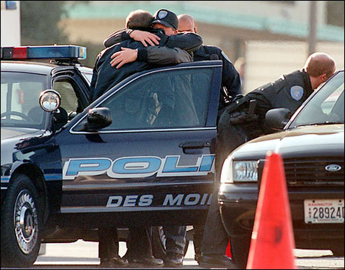 Police officers comfort each other after Des Moines Officer Steven Underwood was shot to death yesterday while checking out a group of teens on Pacific Highway South.