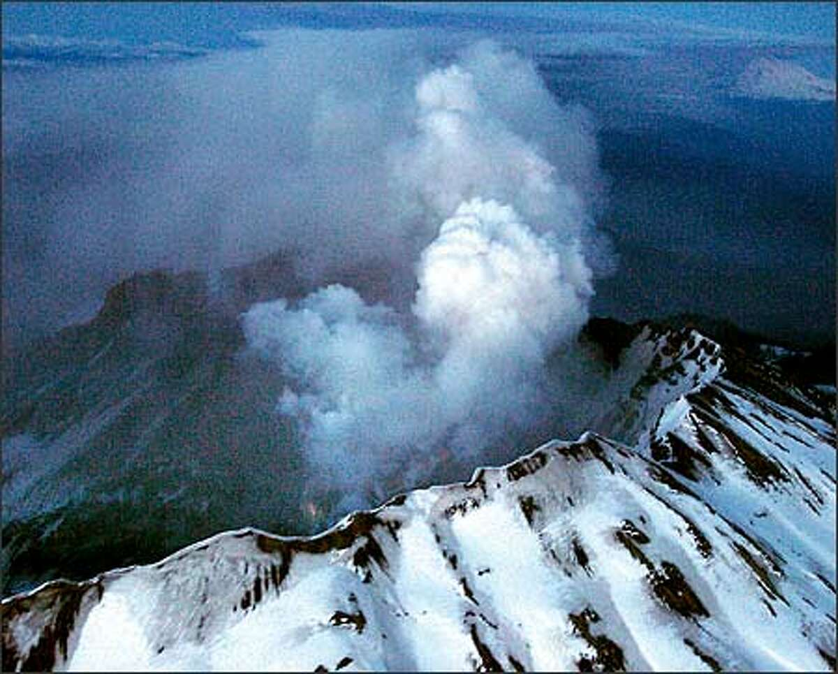 Mount St. Helens showing the plume of ash drifting eastward and a faint glow of molten rock from the new dome from the March 8th explosion at 5:25 p.m. (Kim Blau/The Columbian)