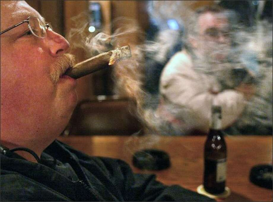 "Jeff Allen of Seattle drove to Tacoma to puff on his cigar at the Pegasus Restaurant on Puyallup Avenue Jan. 21, 2004, in support of a mass ""smoke-in."" Smokers are responding to a smoking ban in Pierce County. Superior Court Judge Ronald Culpepper overturned the county health department's new ban on indoor smoking, which had been challenged in court by a coalition of business owners. Culpepper's ruling is subject to appeal. (AP Photo/The News Tribune, Drew Perine) Photo: Associated Press / Associated Press"