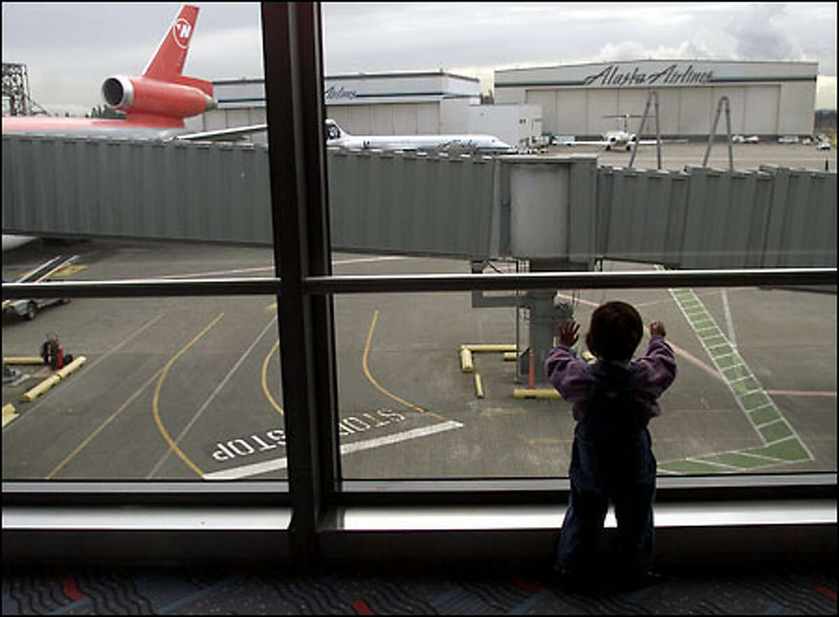 Two-year-old Elisabeta Andrus looks out at Sea-Tac Airport as she waits to go home to Romania, able to really see for the first time after cataract surgery.