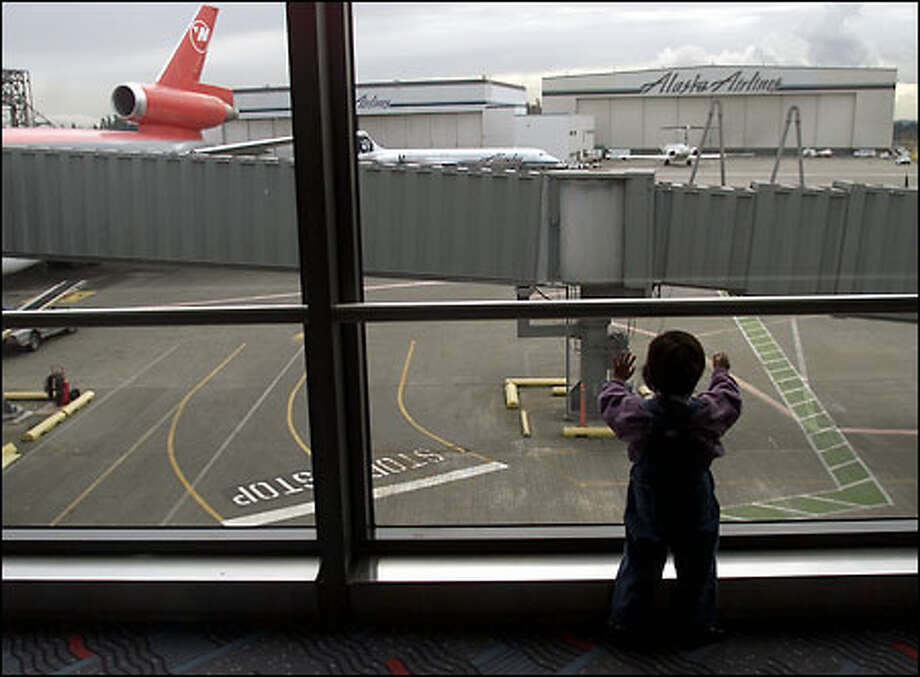 Two-year-old Elisabeta Andrus looks out at Sea-Tac Airport as she waits to go home to Romania, able to really see for the first time after cataract surgery. Photo: Paul Kitagaki Jr., Seattle Post-Intelligencer / Seattle Post-Intelligencer