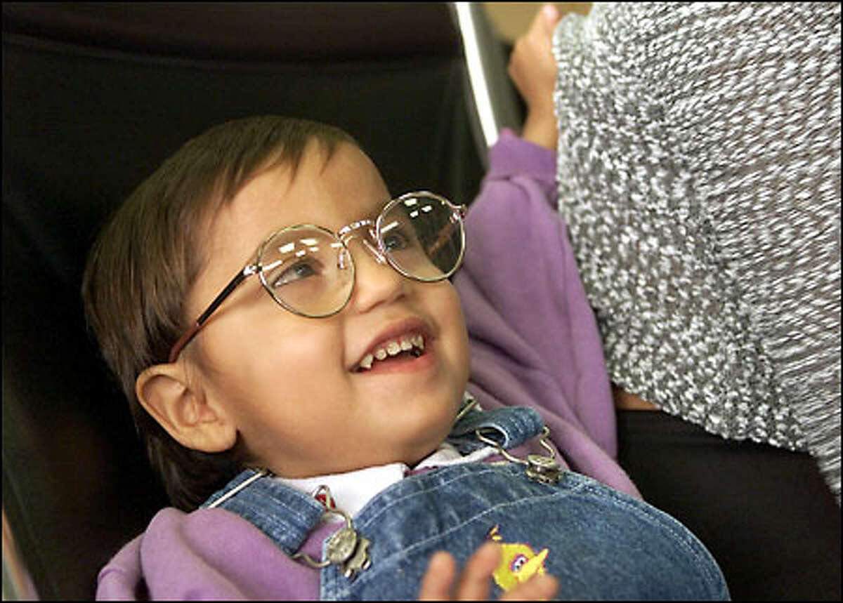 Elisabeta looks at her wonderful new world through shiny new glasses. Someday, it is hoped, she will read and write.