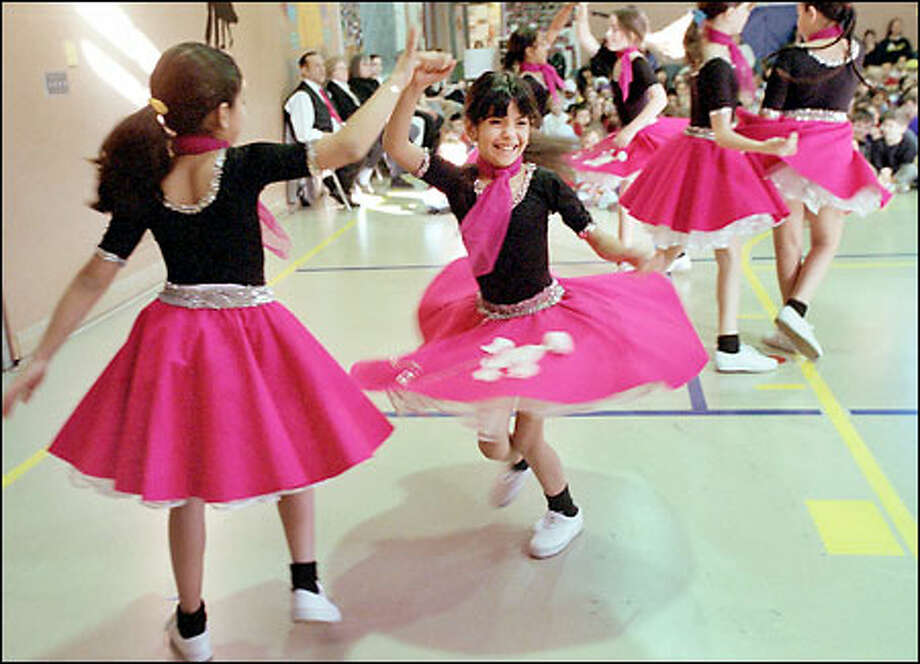 Oh, what happy feet: Esmeralda Alcazar Diaz, 9, left, twirls a beaming Norma Garcia Aguilar, 8, during a ballroom dance performance by the Hilighters at B.F. Day Elementary School. Photo: Renee C. Byer, Seattle Post-Intelligencer / Seattle Post-Intelligencer
