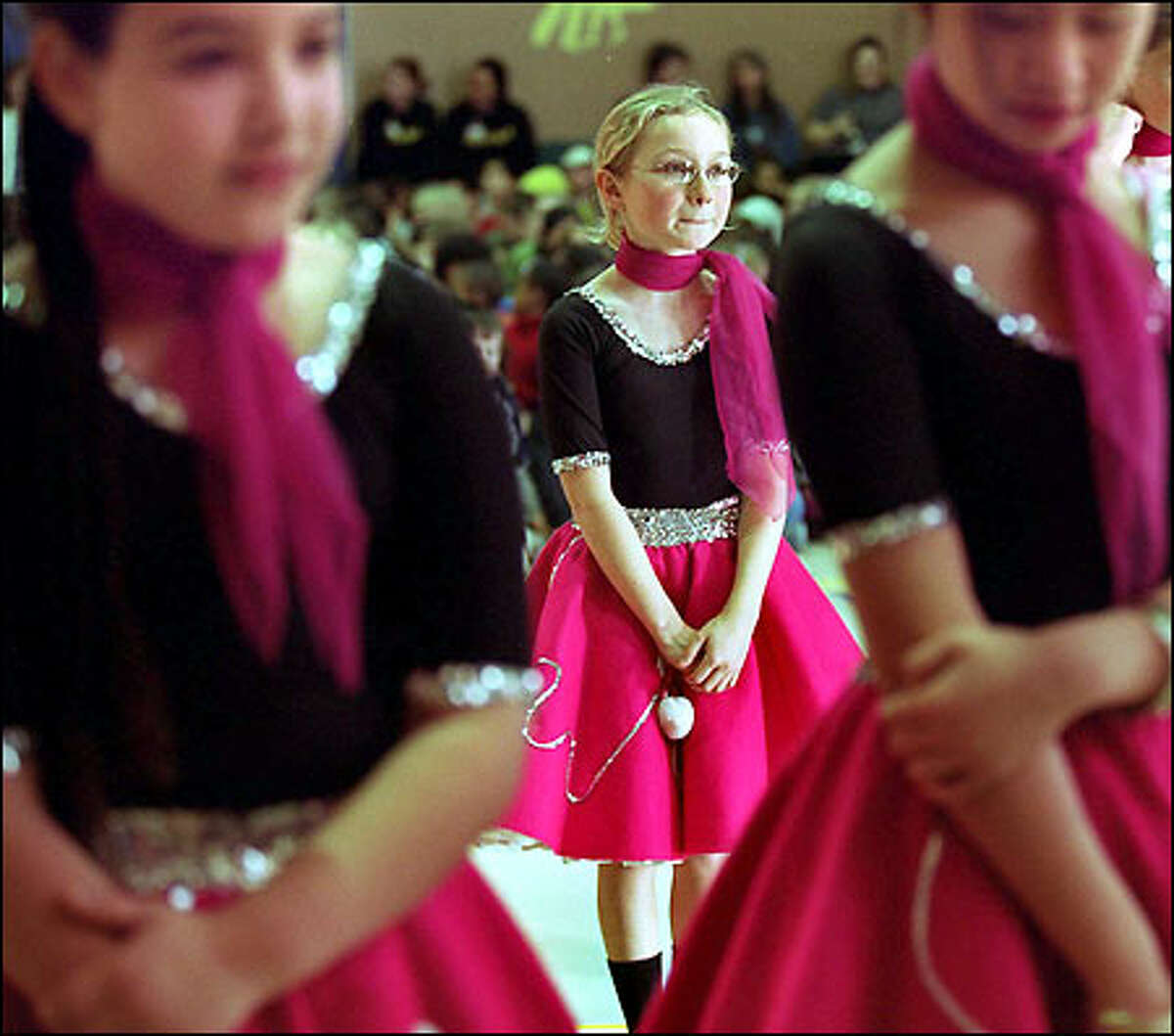 Barely able to contain herself, Miranda York, 10, awaits the start of her dance. She's framed between Anna Elberier, 9, left, and 10-year-old Heidi Saechao.