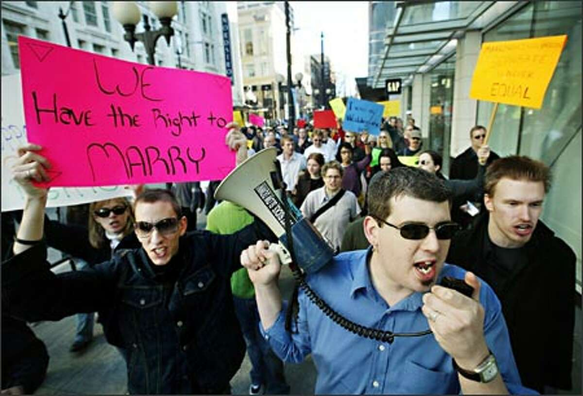 Partners D.J. Klaudt, left, and Brian Peters, with megaphone, lead a march of supporters of gay marriage along Fifth Avenue in downtown Seattle.