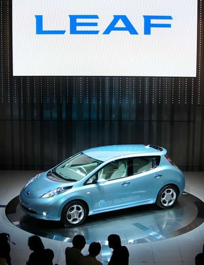 "Photographers take pictures of the new Japanese Nissan Motor's electric vehicle called ""Leaf"" during the opening ceremony for the new company headquarters in Yokohama, Kanagawa prefecture, on Aug. 2, 2009. Nissan will release the electric vehicle in 2010. Photo: Getty Images / Getty Images"