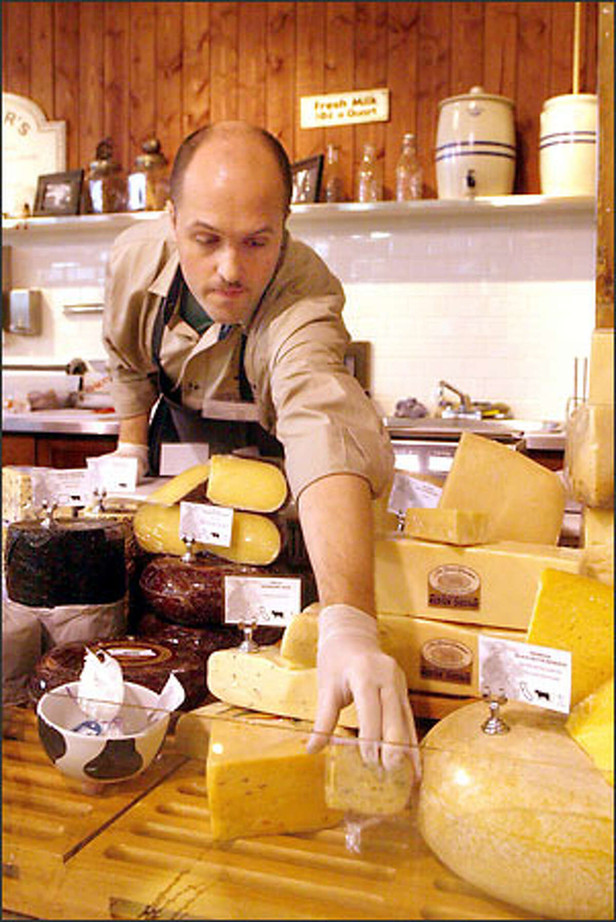 """Cheesemonger Dean Volker loads a display case at Beecher's. Everything edible in the shop is """"clean,"""" meaning it does not have any artificial preservatives."""