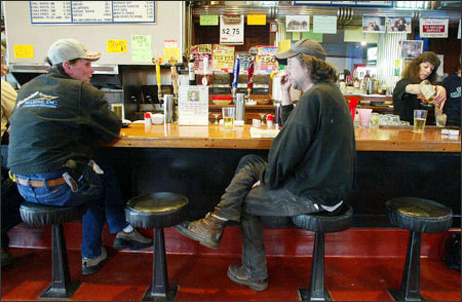 At in Ballard, beer drinkers Cockroach Johnson, left, and Chris Raney chat as bartender Jak Zagars, right, mixes a customer's cocktail. Photo: Gilbert W. Arias, Seattle Post-Intelligencer / SEATTLE POST- INTELLIGENCER