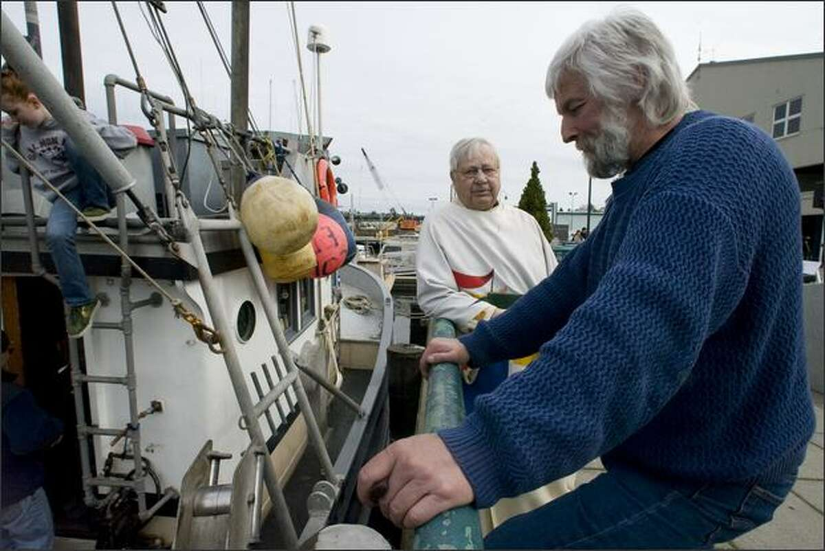 Pastor Emeritus Malcolm Unseth of Ballard First Lutheran Church, left, talks to Paul Mason, owner of the fishing boat Anita, Sunday at the Blessing of the Fleet.