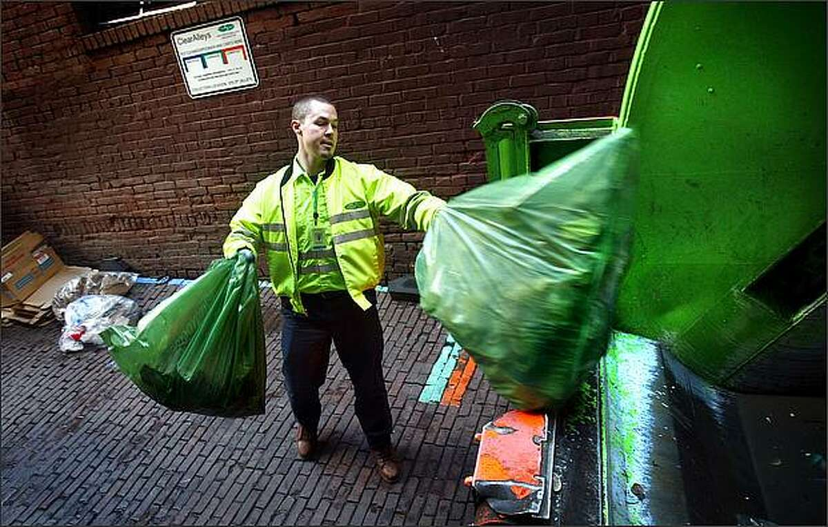 CleanScapes employee Jeremy Simatic tosses trash contained in a prepaid bag into his truck in the alley alongside Chuck's Hole in the Wall Barbeque in Pioneer Square on Monday. The city of Seattle's new Clear Alley's Program will ban the permanent storage of Dumpsters in alleys or sidewalks in Downtown, Belltown and Pioneer Square. Instead, businesses will put refuse, recycling and compost in pre-paid bags that are set directly on the street and collected multiple times each day.