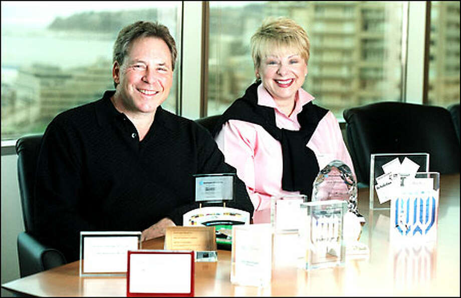 Craig Tall and Dyan Beito, key executives in Washington Mutual's acquisitions strategy, display mementos of some of the company's 32 deals. Photo: Paul Joseph Brown, Seattle Post-Intelligencer / Seattle Post-Intelligencer