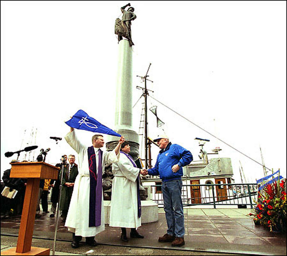 """Pastors Erik Wilson Weiberg, left, and Laurie Jones present a """"Christ pennant"""" to Norman Ness, owner of the Carol M, seen in the background. The Blessing of the Fleet was held yesterday at Fishermen's Terminal."""