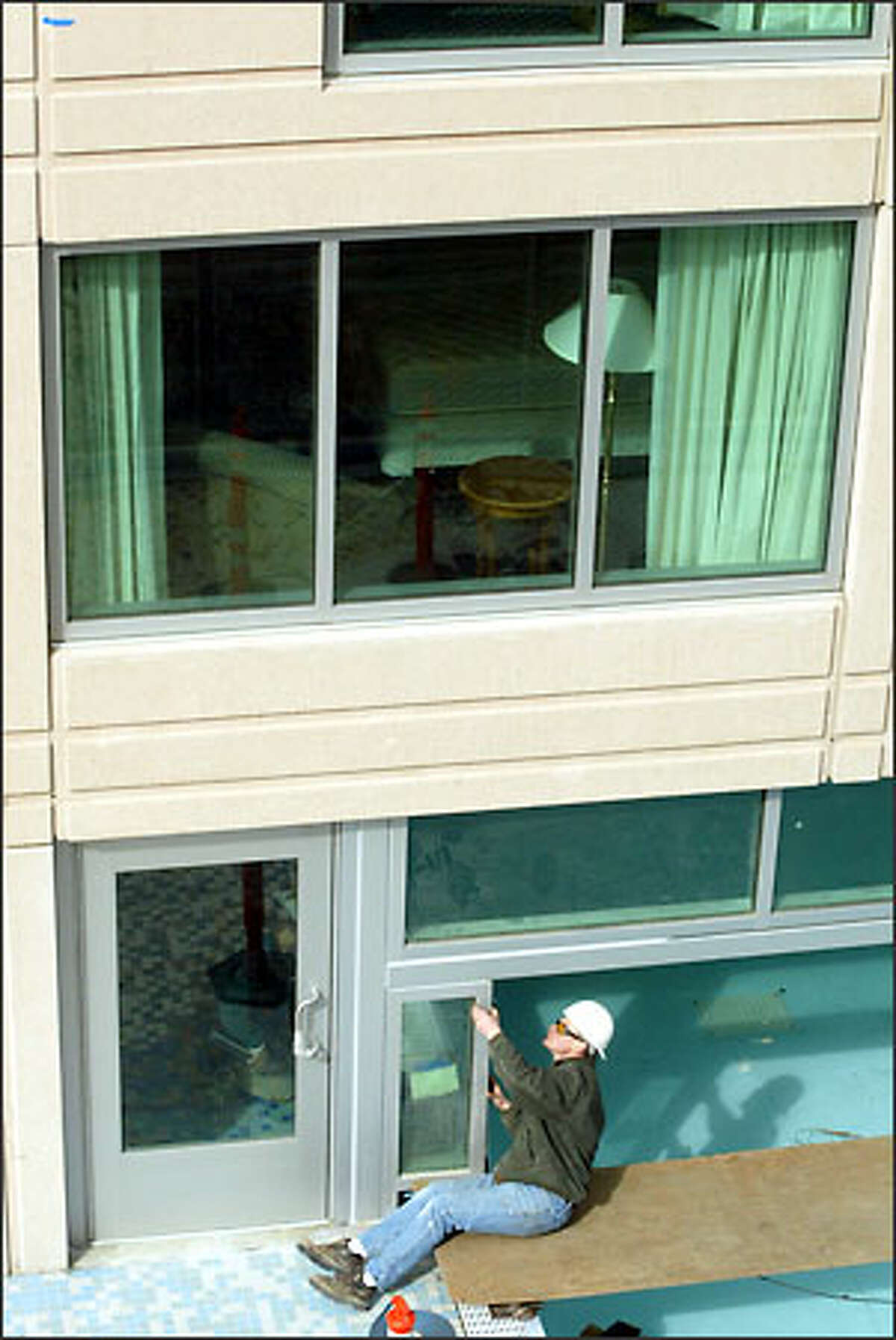 A worker who didn't want to be identified puts stripping around a window next to the indoor-outdoor swimming pool being built for the Seattle Marriott Waterfront Hotel, which is scheduled to open in April.