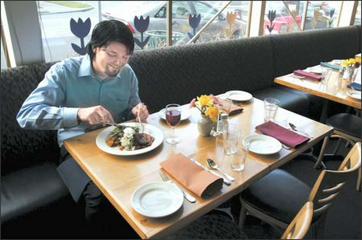 Joe Wiens savors a vegetarian entree at Cafe Flora. The Seattle restaurant will be one of several offering free food samples this weekend at Vegfest, along with 100 food manufacturers and markets.
